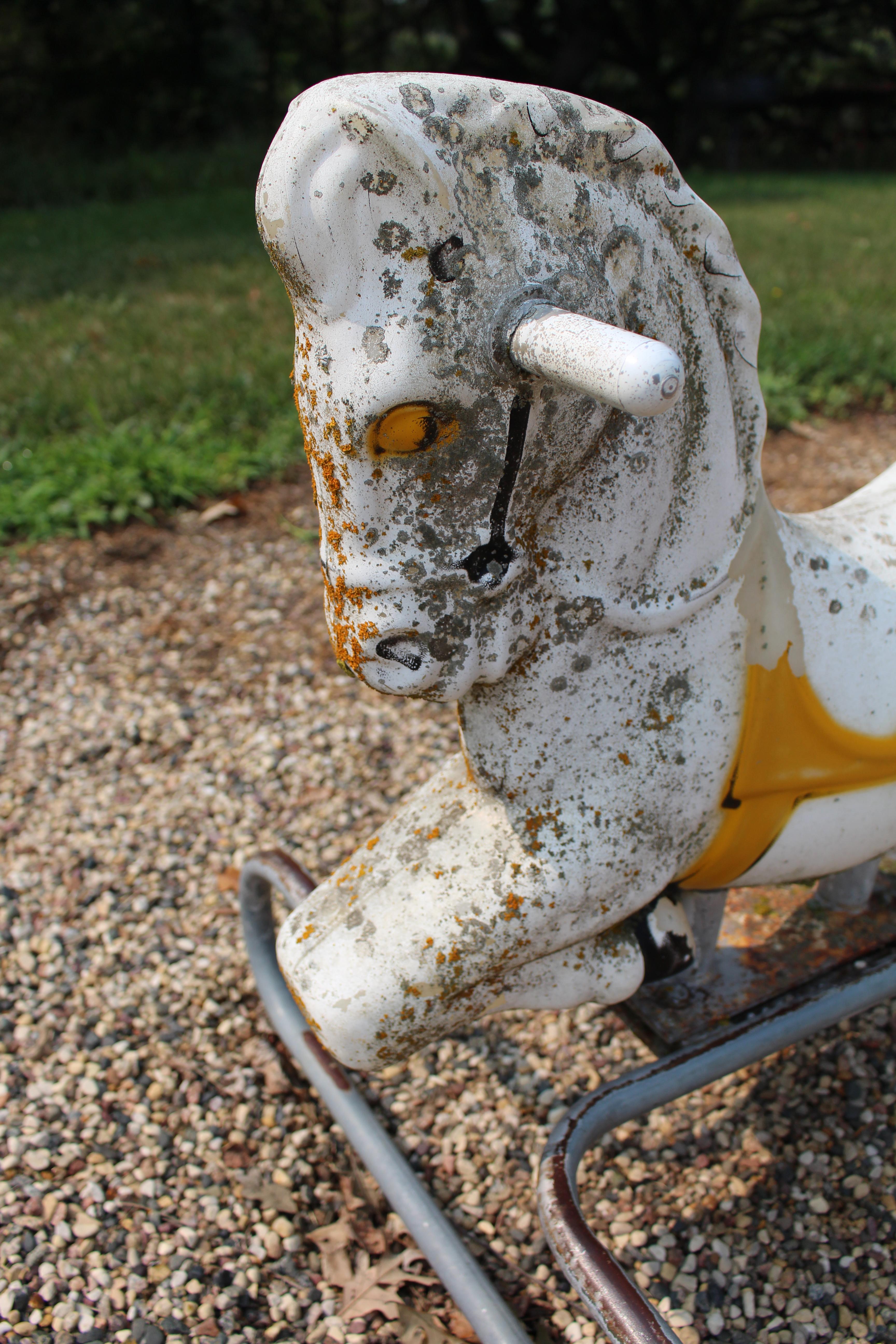 decaying rocking horse riding playground equipment