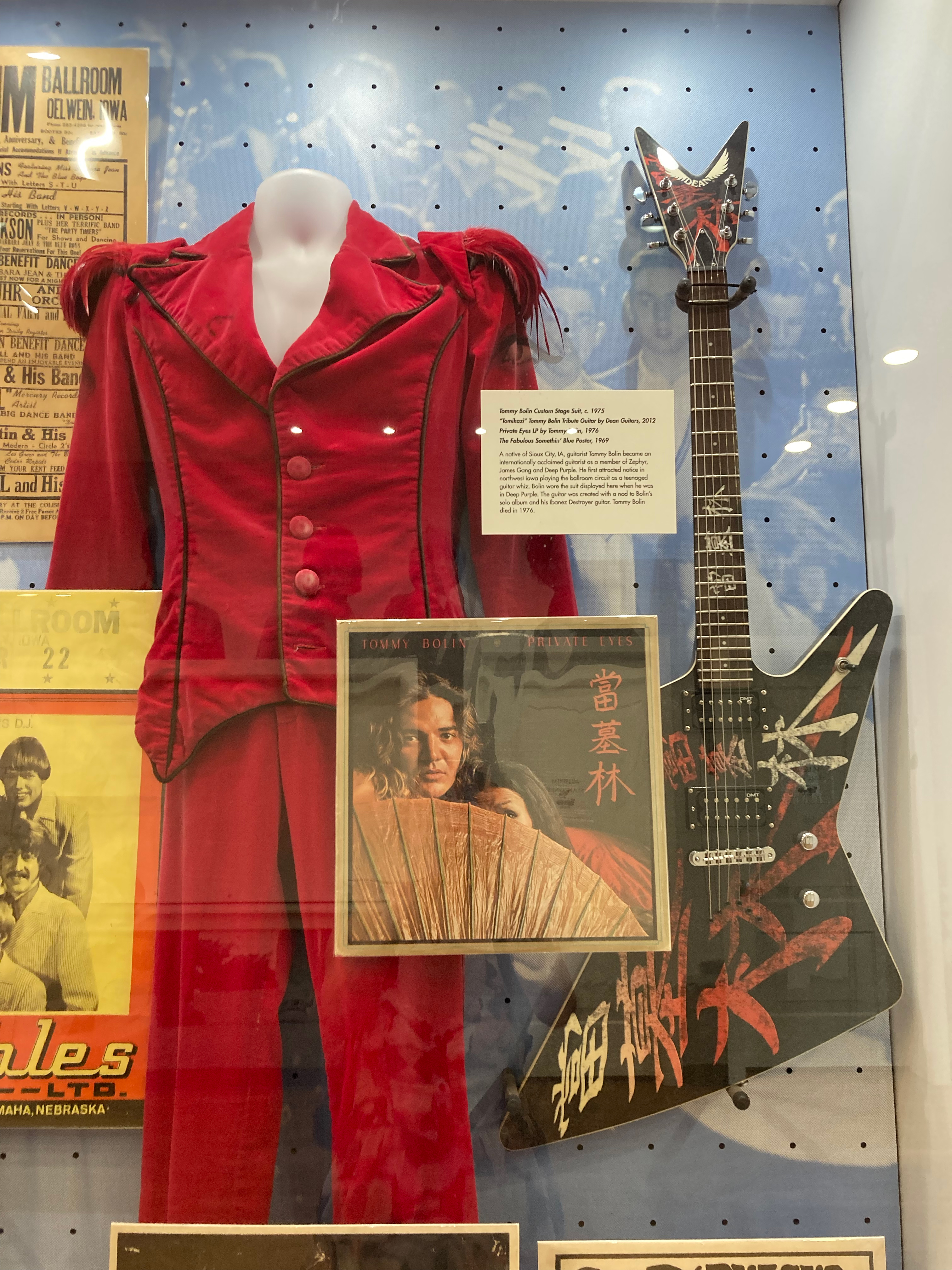 A guitar, velvet pantsuit, and a record with a woman and a fan on the cover in a display case